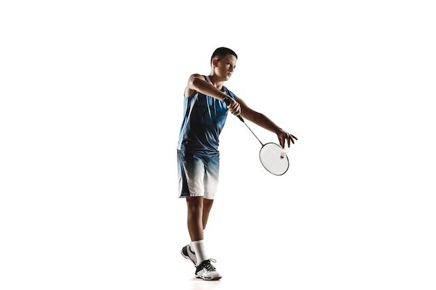 Kleiner junge, der badminton spielt, isoliert auf weißer wand
