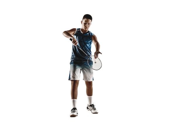 Kleiner junge, der badminton spielt, lokalisiert auf weißem studiohintergrund. junges männliches model in sportbekleidung und turnschuhen mit dem schläger in aktion, bewegung im spiel. konzept des sports, der bewegung, des gesunden lebensstils.