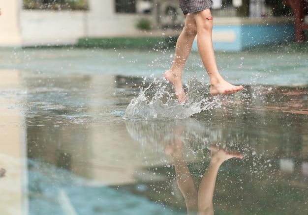 Kleiner junge, der ball im wasser tritt, der auf der straße protokolliert