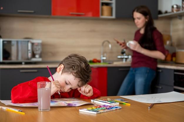 Kleiner junge, der bilder auf küche mit mutter zeichnet