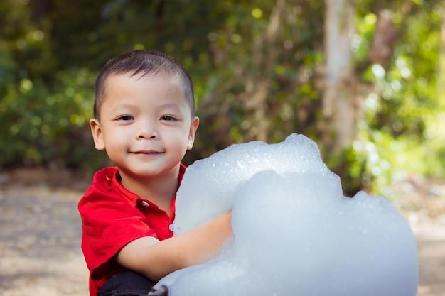 Kleiner junge, der bläst und seifenblasen macht, die blase in seiner hand halten
