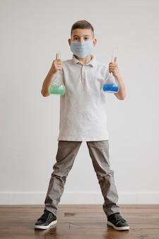 Kleiner junge, der chemische elemente in empfängern hält