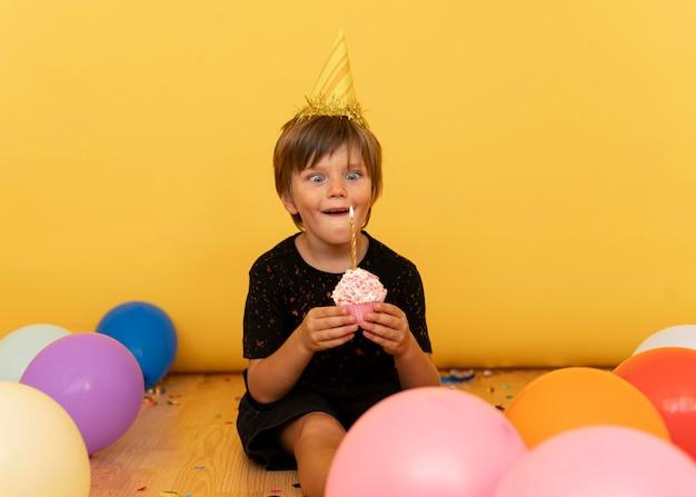 Kleiner junge, der cupcake mit kerze hält