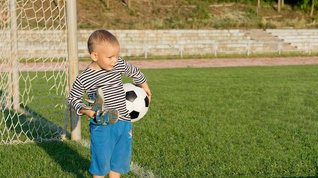 Kleiner junge, der darauf wartet, mit seinen schuhen in der einen und einem fußball in der anderen hand vor den toren fußball zu spielen