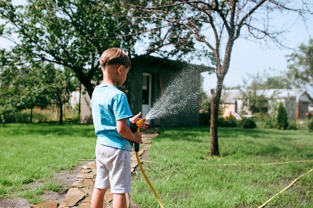 Kleiner junge, der das rasengarten- und pflanzenpflegekonzept wässert