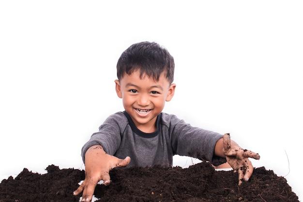 Kleiner junge, der den boden für das pflanzen vorbereitet