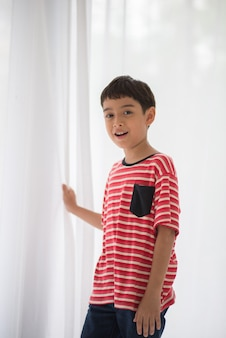 Kleiner junge, der den weißen vorhang öffnet