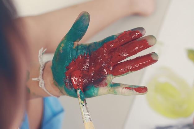 Kleiner junge, der die hände gemalt in den farben zeigt