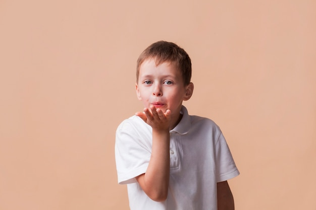 Kleiner junge, der die kamera durchbrennt einen kuss mit der hand auf luft betrachtet