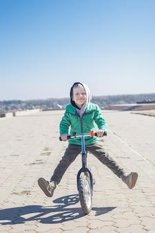 Kleiner junge, der die tricks reiten fahrrad tut