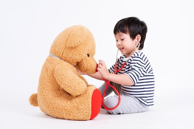 Kleiner junge, der doktor mit teddybären spielt