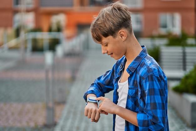 Kleiner junge, der draußen blaue smartwatch spielt.