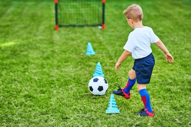 Kleiner junge, der draußen fußball übt
