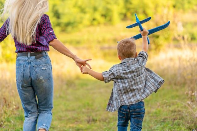 Kleiner junge, der draußen mit spielzeugflugzeug mit seiner jungen mutter bei sonnenuntergang spielt. glückliches kind spielt im park draußen.