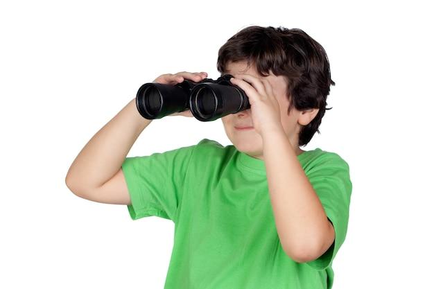 Kleiner junge, der durch die ferngläser getrennt auf weißem hintergrund schaut