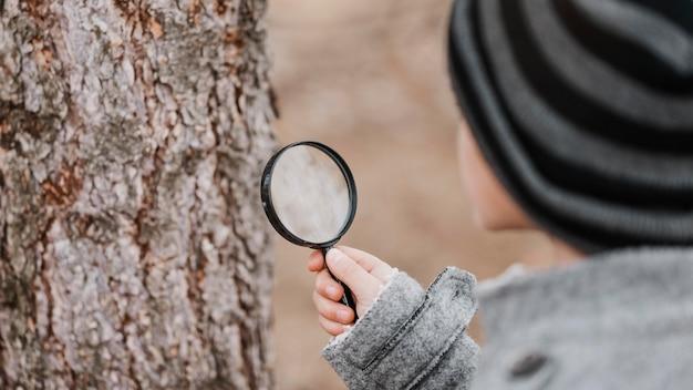 Kleiner junge, der durch eine lupe draußen schaut