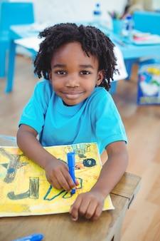 Kleiner junge, der ein bild zeichnet