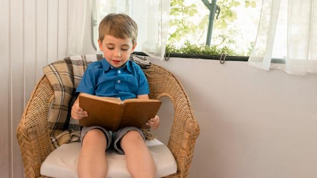 Kleiner junge, der ein buch liest, während er auf einem sessel in einem wohnwagen sitzt