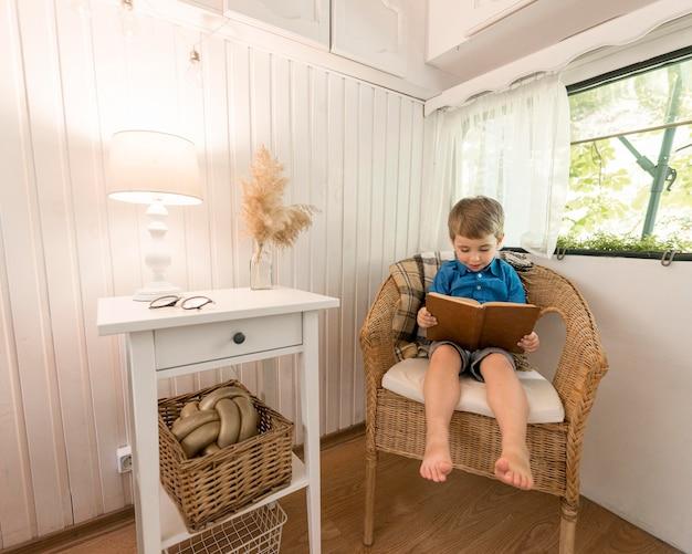 Kleiner junge, der ein buch liest, während er auf einem sessel sitzt