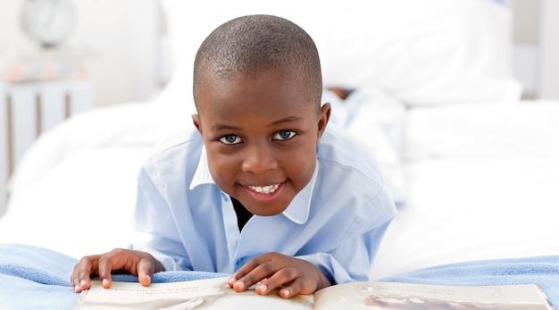 Kleiner junge, der ein buch liest