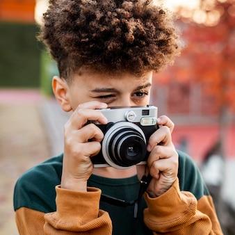 Kleiner junge, der ein foto mit seiner kamera draußen macht