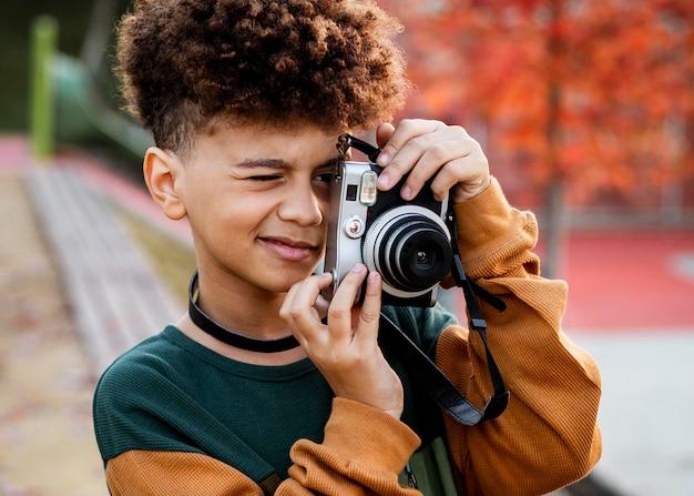 Kleiner junge, der ein foto mit seiner kamera macht