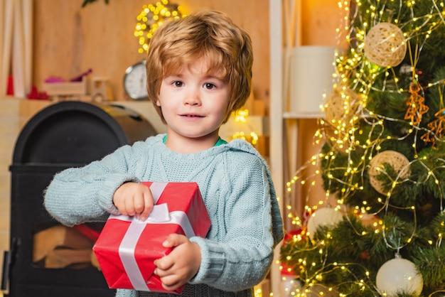 Kleiner junge, der ein geschenk nahe einem weihnachtsbaum hält