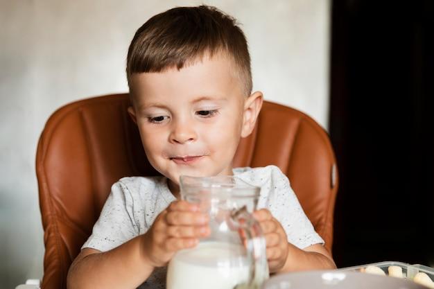 Kleiner junge, der ein glas milch hält