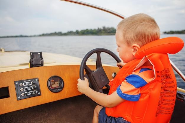 Kleiner junge, der ein motorboot auf fluss fährt, der das lenkrad fest hält