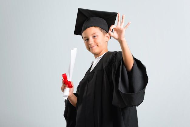 Kleiner junge, der ein okayzeichen mit den fingern auf grauem hintergrund zeigend graduiert