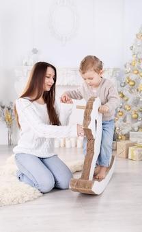 Kleiner junge, der ein papppferd nahe dem weihnachtsbaum reitet