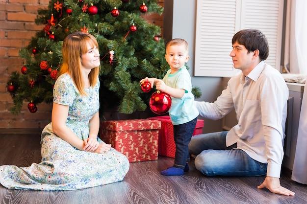 Kleiner junge, der ein weihnachtsbaumspielzeug verziert. feiertags-, geschenk- und neujahrskonzept.