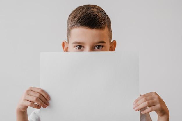 Kleiner junge, der ein weißes papier hält