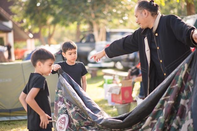 Kleiner junge, der ein zelt für das kampieren mit familienfeiertags-sommerzeit errichtet