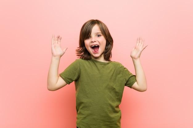 Kleiner junge, der eine angenehme überraschung empfängt, aufgeregt und hände anhebend.