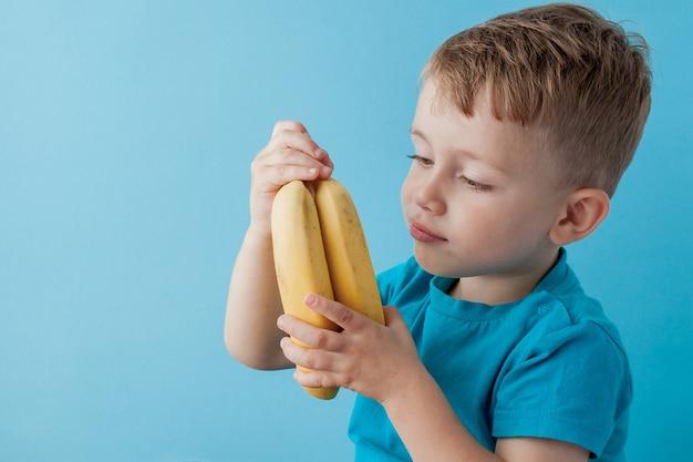 Kleiner junge, der eine banane auf blauer wand, essen, diät und gesundes ernährungskonzept hält und isst.