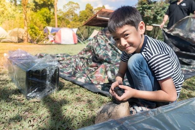 Kleiner junge, der eine camp tent-sommerzeitaktivität im freien mit familie macht