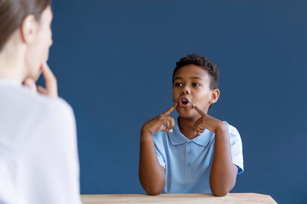 Kleiner junge, der eine ergotherapiesitzung mit einem psychologen hat