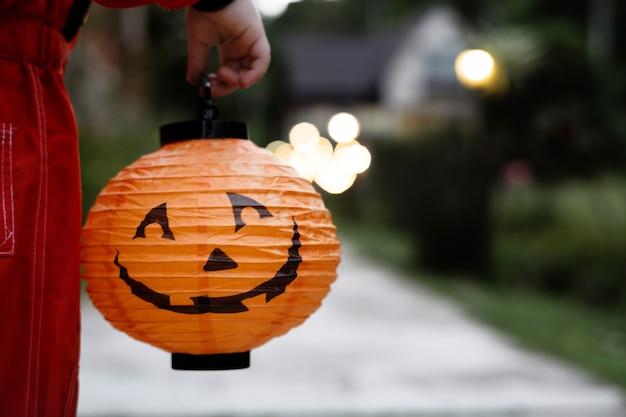 Kleiner junge, der eine halloween-laterne hält