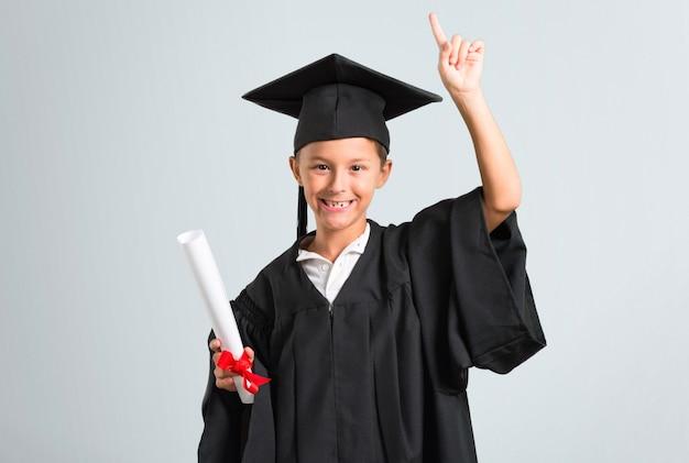 Kleiner junge, der eine idee auf grauem hintergrund stehend und denkend graduiert