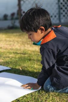 Kleiner junge, der eine kittelhand trägt, die an einem sonnigen tag im hinterhof eine weiße oberfläche malt