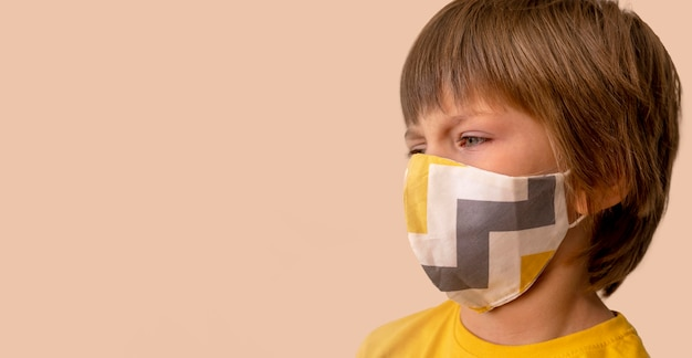 Kleiner junge, der eine medizinische maske trägt