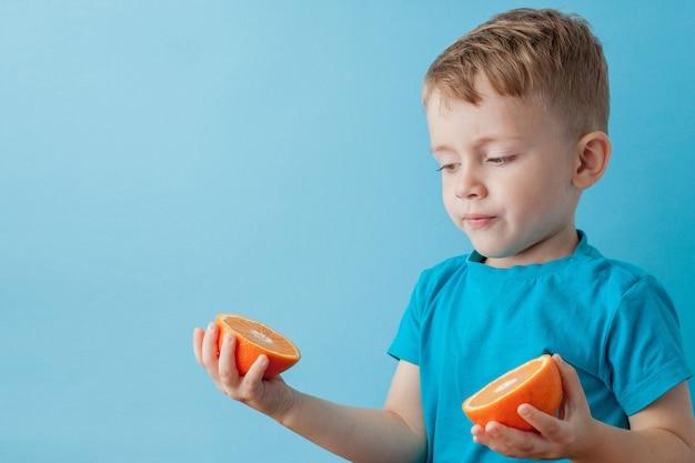 Kleiner junge, der eine orange in seinen händen auf blauem hintergrund, diät und übung für gutes gesundheitskonzept hält.