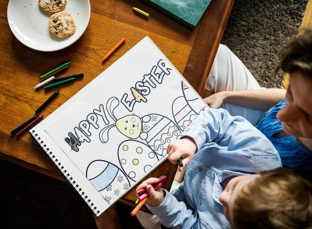 Kleiner junge, der eine ostern-zeichnung bildet