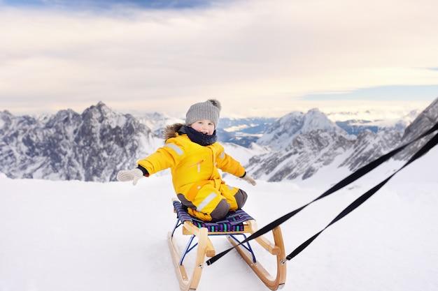 Kleiner junge, der eine pferdeschlittenfahrt genießt. kinderschlitten in den alpenbergen im winter