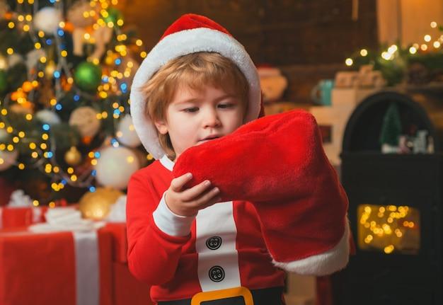 Kleiner junge, der eine rote santa socke drinnen hält