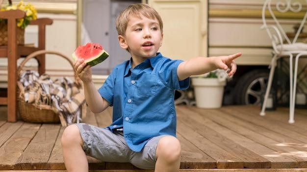 Kleiner junge, der eine scheibe wassermelone hält