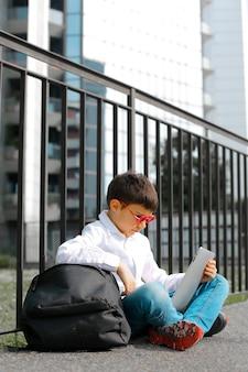 Kleiner junge, der eine tablette auf der straße verwendet
