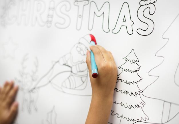 Kleiner junge, der eine weihnachtszeichnung malt