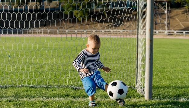 Kleiner junge, der einen ball aus den toren tritt, während er fußball auf einem üppigen grünen feld spielt